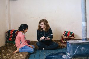 Hayley Smith reads to a young refugee girl.