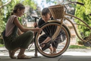 A mother bends down as she helps her daughter pump up a bicycle tire.