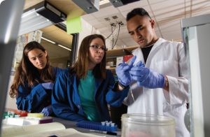 Keni Reed and two female students examine a miniature test tube in the Kauwe Lab.