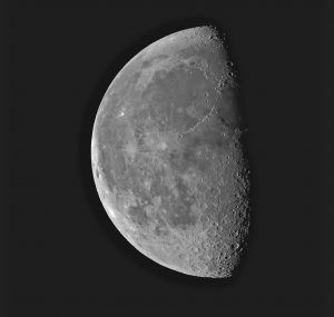 A photo of the moon. The moon is half shaded in darkness.