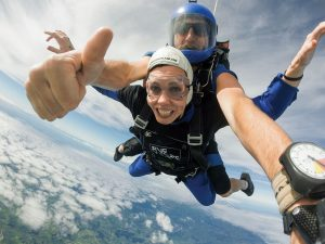 A woman and instructor skydiving over New Zealand.