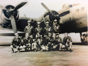A WWII bomber crew posing in front of a B-17 bomber.