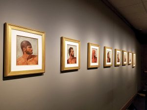 A line of portraits along the wall showing a man's head.