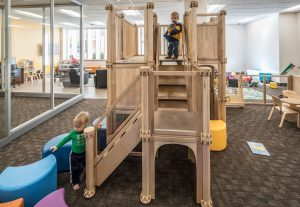 Kids play on the play structure n the new family study room
