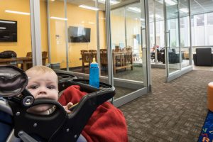 A baby teethes on the handle of its stroller n the new family study room