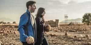 Jordan Kamalu and Danielle Calder-Kamalu walk through McCoard's Garden Center, holding gourds.