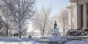 A photo of snow covered trees and the Karl G. Maeser statue covered in snow outside the Maeser building on BYU campus.