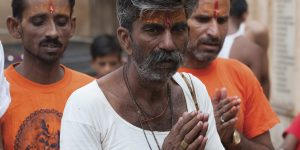 Three Indian men with red paint on their foreheads and their hands clasped in prayer.
