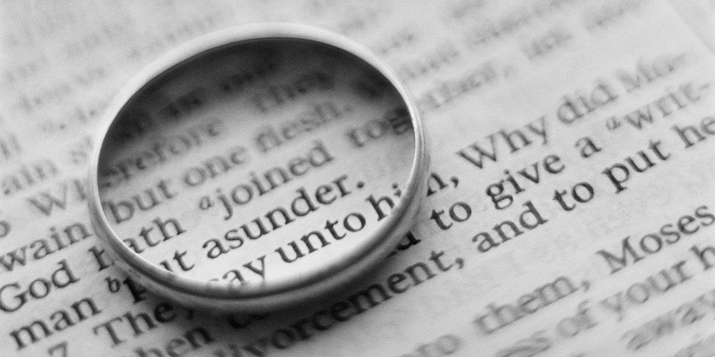A photo of a wedding ring lying on top of a text. The ring circles the word