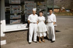 Stanley Taylor, Sarah Taylor, and Ron Taylor stand in front of Stan's Drive-In on 5th North and 9th East.