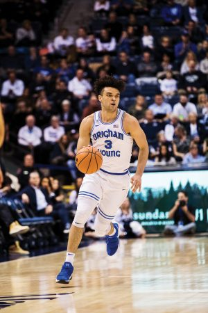 Photo of Elijah Bryant dribbling the basketball in a game.