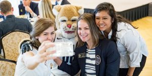 BYU Alumni president Amy Fennegan poses with students and Cosmo the cougar at an Alumni event.