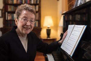 Poet and hymn writer Karen Davidson sitting at a piano.