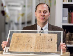 BYU professor holding papyrus scrolls