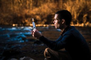 BYU professor Ben Abbott looking at a syringe, crouched in a stream.