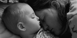 A black and white photo of a mother and child sleeping together.