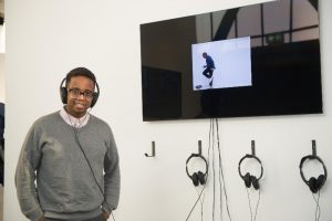 Julian Harper, wearing headphones, standing next to a television screen playing his award-winning video.