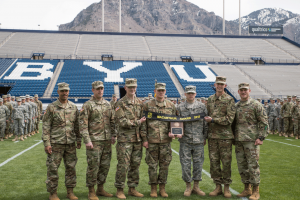 Members of BYU Army ROTC stand on the field in LaVell Edwards Stadium holding the banner for the MacArthur Award