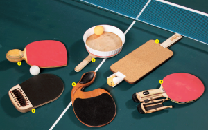 A photograph of six unique ping pong paddles lying on a ping pong table.