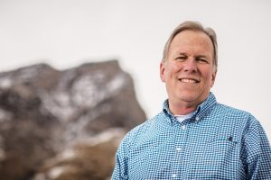Backed by a mountain peak, BYU grad Joseph Johnston stands and smiles.