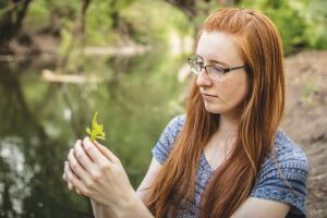 Anne Thomas holding a yellow flower next to a green river
