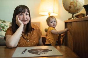 Her daughter playing in the background, Cindy Bean sits at a desk with one of her paper-cut creations.