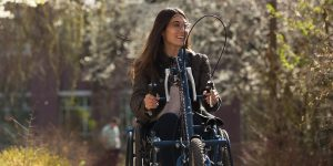 A young woman using a hand-trike wheel chair attachment.