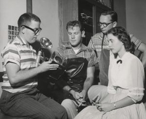 Three students gather around an instructor, who teaches the students how to use a camera and flash in 1957.