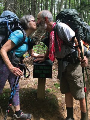 John and Shauna Dickson kiss over a trail sign on the Appalachian Trail