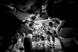 A black and white photo of the men's volleyball team in a huddle.