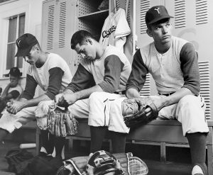 Three BYU baseball players look discouraged after being unable to compete in the College World Series.