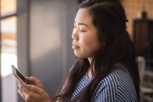 A young woman holding a smartphone launches an app, closes her eyes, and practices breathing exercises.