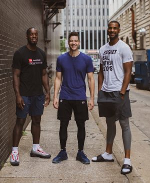 Charles Abouo, Jimmer Fredette, and Brandon Davis pose together.