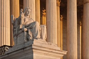 A marble statue outside the U.S. Supreme Court of a woman sitting in a chair acting as a judge.