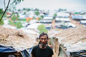 A Rohingya man walks in between grass huts in a refugee camp.