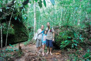 Fernanda Werneck and Rafael Leite, scientists at the National Institute for Amazon Research in Manaus, Brazil, stand in a patch of Amazon forest with their daughter, Iara.