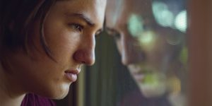 A despondent teen leans against his reflection in a window pane.