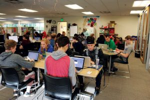 High school students work on college prep coursework on laptops in a classroom.