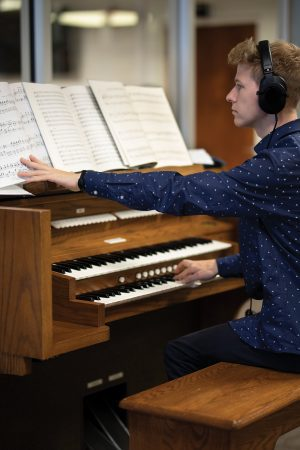 While wearing headphones, a student practices on an electric organ.