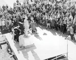 An old photo of the unveiling of the Karl G. Maeser statue placed outside of a building with a crowd and photographers gathered around to see it.