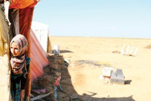 A Syrian refugee woman is looking out from her tent in the Jordanian desert.