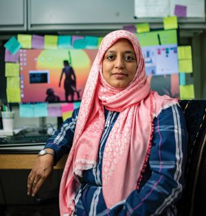 PhD student Meher Shaikh sits in front of her computer, which is ringed with colorful sticky notes.