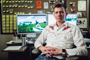 Brad Barber, in an embroidered shirt, sits in his office with footage of States of America on the monitor in the background.