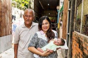 A Cambodian woman holds her baby outside their home. Her father stands behind them.