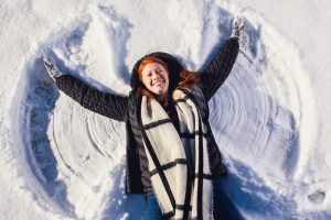 Lying in the snow, Emma Stanford makes a snow angel.