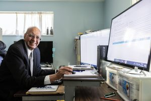 Gurcharan Gill smiles from his desk, working on a family history project on the computer.