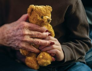 Hands, one young, one old, grasp a golden=brown teddy bear.