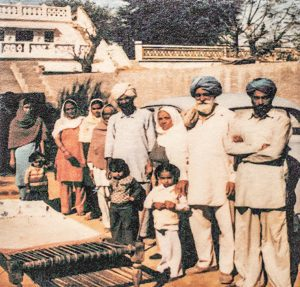An indian family in traditional Indian garb stands in front of their ancestral home and an old-fashioned car. There is a weaving loom on the ground in front of them.