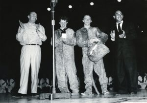 Four people, two of them in Cosmo costume, stand on the playing floor of the Smith Fieldhouse in 1956.