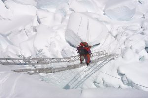 A climber crosses a ladder set across a giant crevasse on Everest.